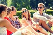 Group of smiling friends outdoors sitting in park — Stockfoto