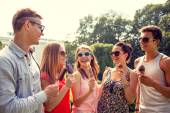 Group of smiling friends with ice cream outdoors — Stock fotografie