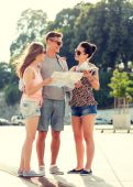 Smiling friends with map and city guide outdoors — Stock fotografie