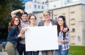 Happy teenage students holding white blank board — Стоковое фото