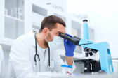 Young scientist looking to microscope in lab — Stock Photo
