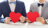 Close up of male gay couple holding red hearts — Stock Photo