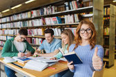 Happy student girl showing thumbs up in library — Stock Photo