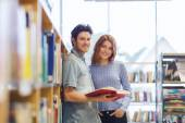 Happy student couple with books in library — Stock Photo