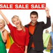 Happy people with red sale sign and shopping bags — Stock Photo #72676711