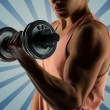 Close up of young man with dumbbell flexing biceps — Stock Photo #72677007