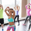 Group of smiling people dancing in gym or studio — Stock Photo #72678401