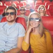 Happy friends watching movie in 3d theater — Stock Photo #72678667