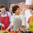 Happy friends and chef cook cooking in kitchen — Stock Photo #72678881