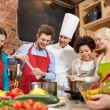 Happy friends and chef cook cooking in kitchen — Stock Photo #72678913