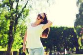 Uśmiechnięta młoda kobieta z okulary w parku — Zdjęcie stockowe