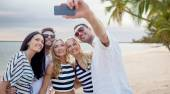 Friends on beach taking selfie with smartphone — Stock Photo