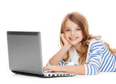 Smiling student girl with laptop computer lying — Stock Photo