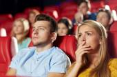 Happy friends watching horror movie in theater — Stock Photo