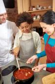 Happy women and chef cook cooking in kitchen — Stock Photo