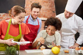 Happy friends and chef cook baking in kitchen — Стоковое фото