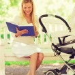 Happy mother with book and stroller in park — Stock Photo #72993663