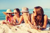 Group of smiling young women with tablets on beach — Stock Photo