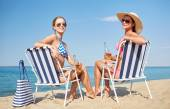 Happy women sunbathing in lounges on beach — Стоковое фото