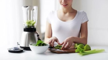 Smiling woman with blender and green vegetables — Stock video