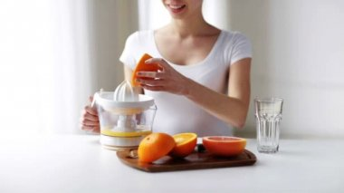 Woman with squeezer squeezing orange juice at home — Stock Video