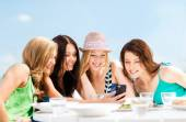 Girls looking at smartphone in cafe on the beach — Foto Stock