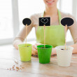 Close up of woman over pots with soil and signs — Stock Photo #73170657