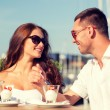 Smiling couple eating dessert at cafe — Stock Photo #73306559