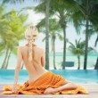 Woman with orange towel over tropical beach — Stock Photo #73306657