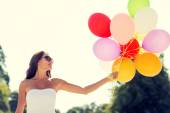 Smiling young woman in sunglasses with balloons — Stock Photo