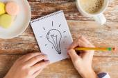 Close up of hands drawing bulb to notebook — Stock Photo