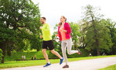 Smiling couple with earphones running outdoors — Stock Photo