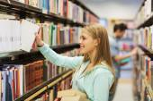 Happy student girl or woman with book in library — Stock Photo