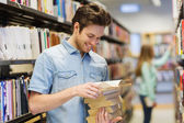 Happy student or man with book in library — Stock Photo