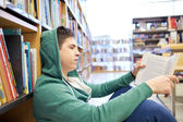Student boy or young man reading book in library — Stock Photo