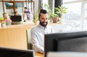 Happy creative male office worker with computer — Stock Photo