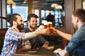 Happy male friends drinking beer at bar or pub — Stock Photo