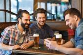 Male friends with smartphone drinking beer at bar — Zdjęcie stockowe