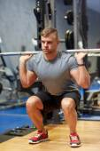 Young man flexing muscles with barbell in gym — Stock Photo