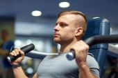 Man exercising and flexing muscles on gym machine — Stock Photo