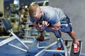 Young man flexing back muscles on bench in gym — Stock Photo