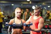 Young couple with dumbbells flexing muscles in gym — Stock Photo