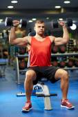 Young man with dumbbells flexing muscles in gym — Stock Photo
