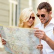 Smiling couple in sunglasses with map in the city — Stock Photo #73377017