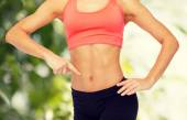 Close up of woman pointing finger at her six pack — Stock Photo