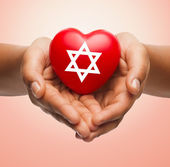 Close up of hands holding heart with jewish star — Stock Photo