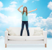 Smiling little girl jumping on sofa — Stock Photo