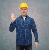 Smiling male builder in helmet showing ok sign — Stock Photo