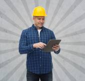 Smiling male builder in helmet with tablet pc — Stock Photo