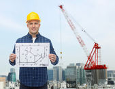 Smiling male builder in helmet with blueprint — Stock Photo